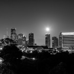 Nearly full moon rising behind the skyline of downtown Houston, TX