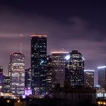 Downtown skyline of Houston lighting up the clouds at night